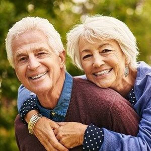 Older man and woman smiling together outdoors