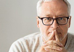 Older man with glasses contemplating
