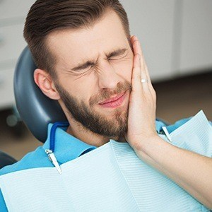 Man in dental chair holding cheek in pain
