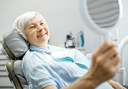 An older lady seated in a dentist's chair looking at her new smile in the mirror