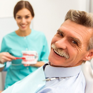An older man sitting in the dentist's chair with a dental hygienist in the background